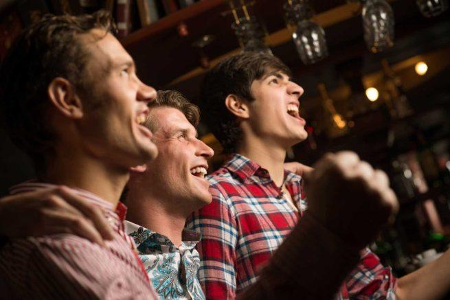 Men cheering at a bar